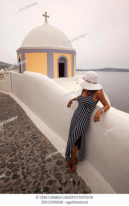 Woman in front of a yellow domed church in Fira town, Santorini, Cyclades Islands, Greek Islands, Greece, Europe