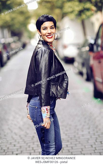Portrait of fashionable young woman wearing jeans and leather jacket