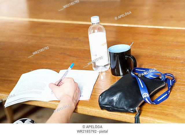 Cropped image of woman writing notes at table in classroom