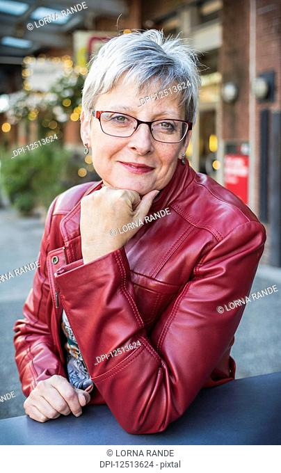 Portrait of a mature woman in a red leather jacket sitting at a table with her chin resting in her hand; Vancouver, British Columbia, Canada