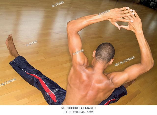Afro-American doing stretching exercise on wooden floor