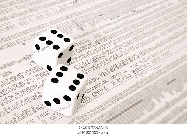 Dice on the stock market section of a newspaper
