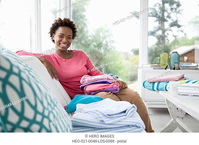 portrait of mid adult woman with folded laundry