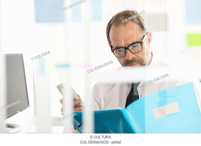 Businessman reading paperwork and using smartphone