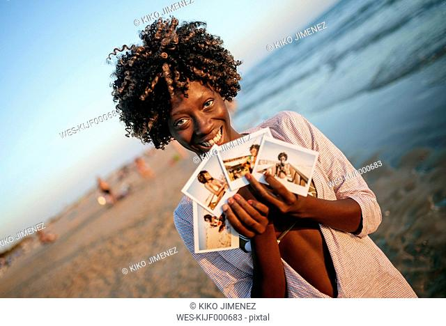 Young woman showing instant photos on the beach