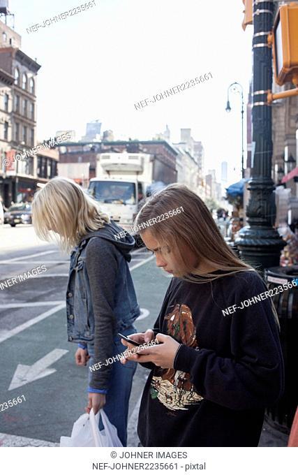 Teenage girl using cell phone on street