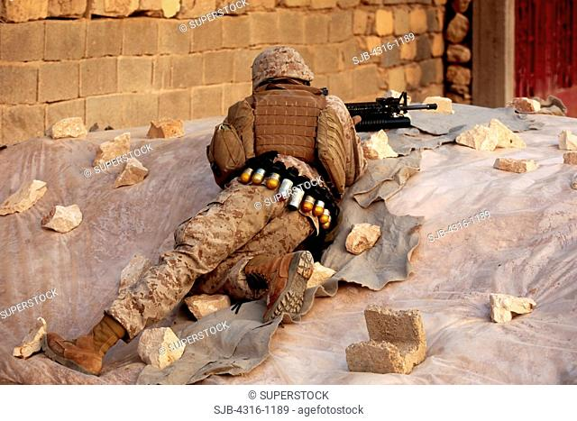 A US Marine Takes Cover During a Combat Operation in the City of Haditha, Iraq
