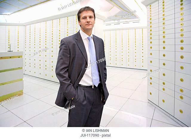 Portrait Of Businessman Standing In Safety Deposit Vault