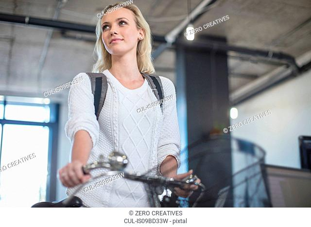 Young woman arriving with bicycle to office