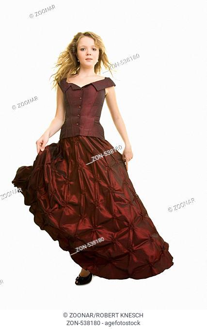 Blondes Mädchen tanzt in einem weinroten Abendkleid