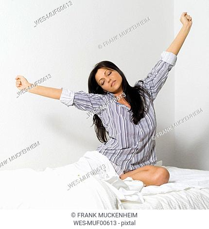 Young woman stretching in bed, portrait