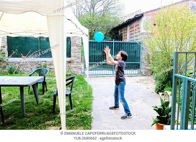 Child in the backyard playing catch