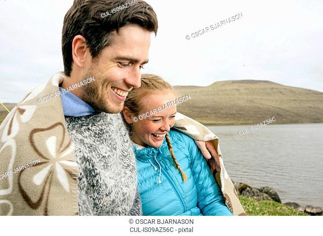 Couple wrapped in blanket by lake, Vagar, Faroe Islands