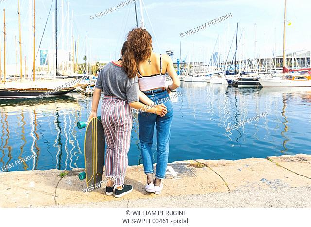 Young woman and teenage girl with a skateboard standing at marina