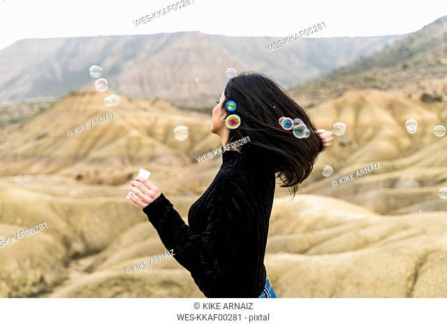Spain, Navarra, Bardenas Reales, young woman blowing soap bubbles