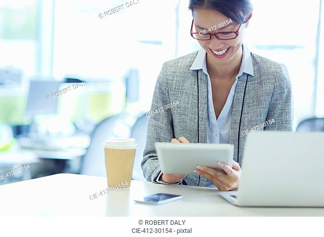 Smiling businesswoman using digital tablet with coffee in office