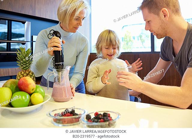 Family in the kitchen. Three generations. Healthy eating. Healthy growth. Making milkshakes with berries