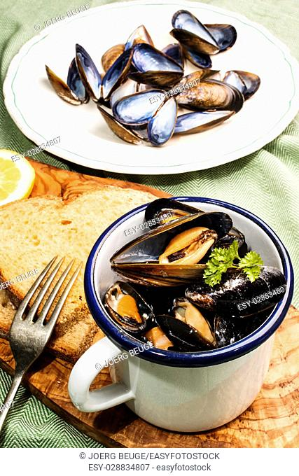 mussels with garlic and butter sauce in a blue and white enamel mug on a wooden board