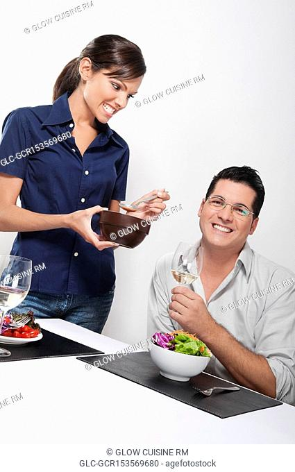 Couple having vegetable salad and drinking white wine