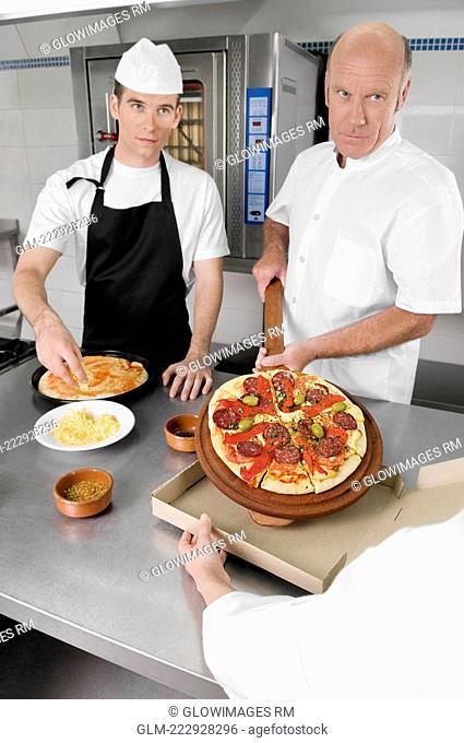 Three chefs preparing pizza in the kitchen