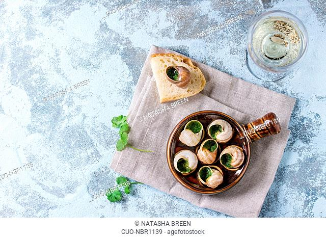 Escargots de Bourgogne - Snails with herbs butter, in traditional ceramic pan with parsley, bread and glass of white wine on textile napkin over blue textured...