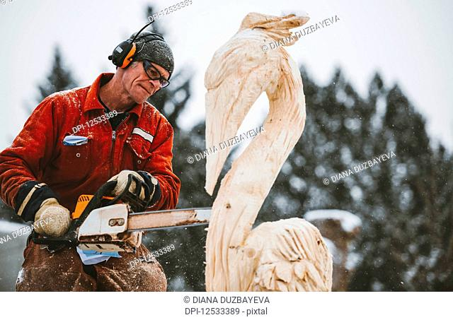 Artist carving a wood sculpture with chainsaw; Edmonton, Alberta, Canada