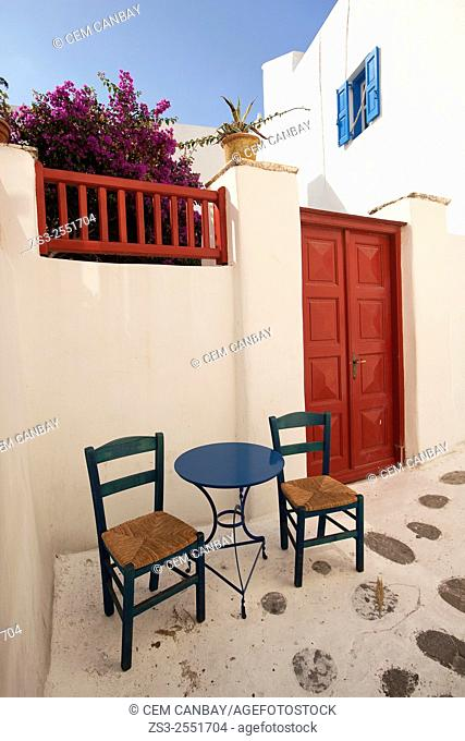 Table and chairs in the corner of a whitewashed house with colorful doors and windows in town center, Mykonos, Cyclades Islands, Greek Islands, Greece, Europe