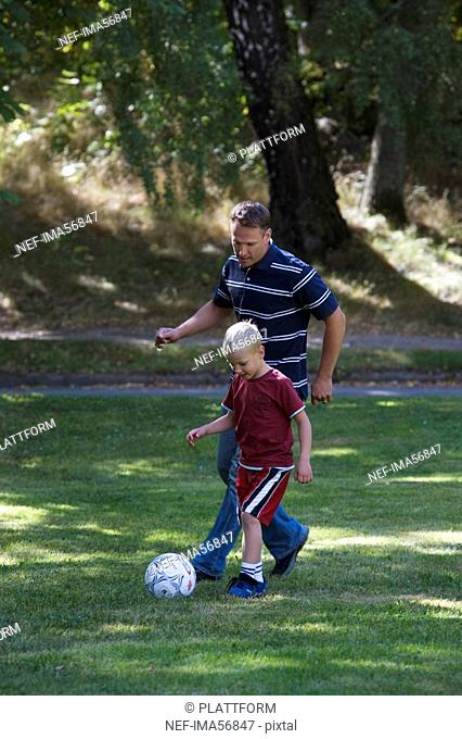 Father and son playing football in a park a sunny day Sweden