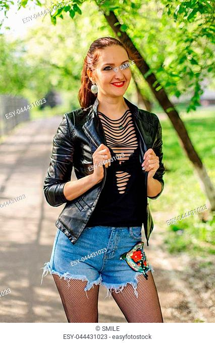 Spring portrait of a charming woman dressed in a leather jacket standing on the road under the bird-cherry tree flower