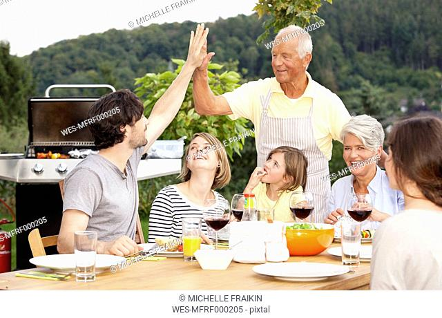 Adult son high fiving father at barbecue party