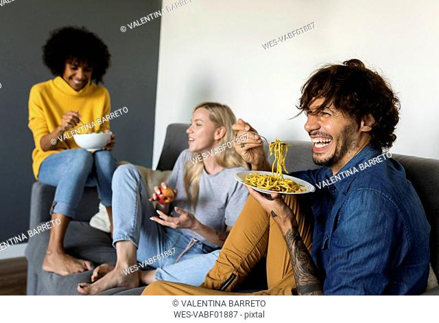 Cheerful friends sitting on couch talking and eating