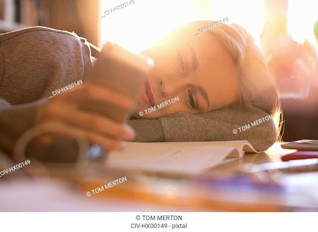 Teenage girl laying and texting with cell phone
