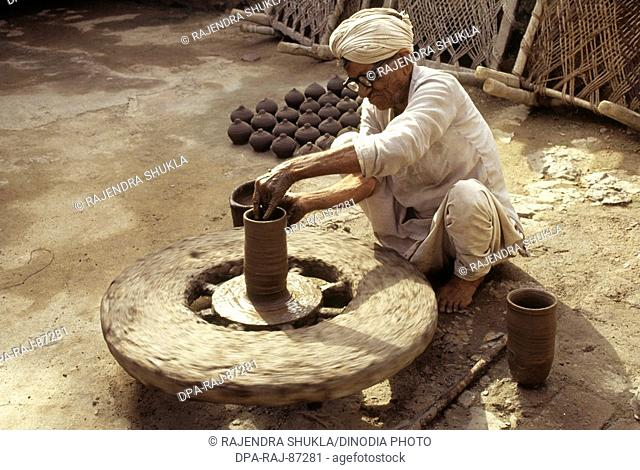 Pottery , potter giving shape to clay pot on wheel