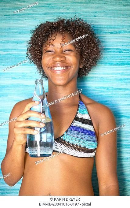 Portrait of woman in bikini with bottled water