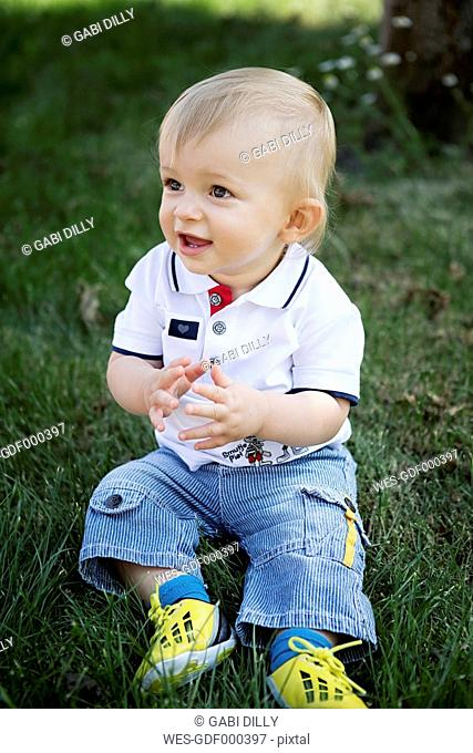 Germany, Oberhausen, Blond baby boy sitting on grass in park