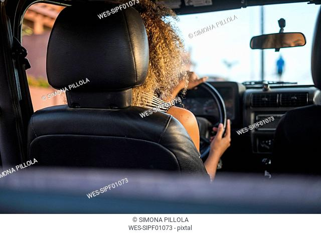 Back view of woman driving car