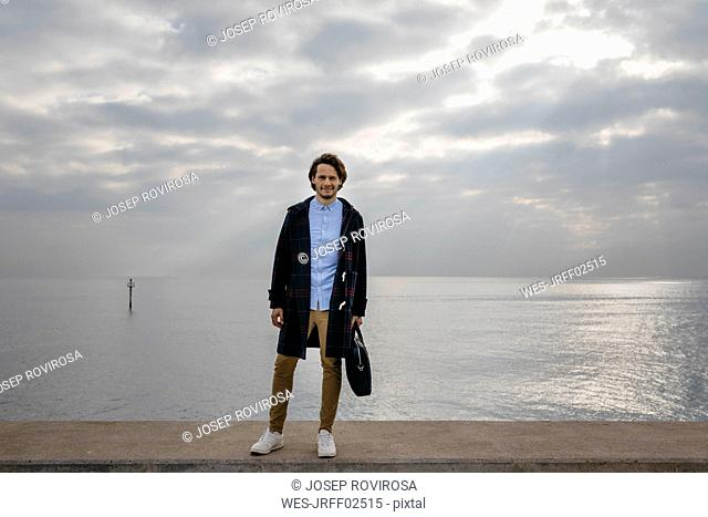 Spain, Barcelona, portrait of confident man with the sea in the background