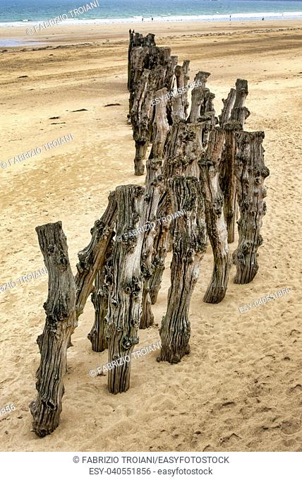 Wooden stakes driven into the sand on the beach at Saint-Malo, Brittany, France