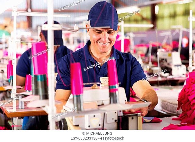 happy senior worker sewing in clothing factory