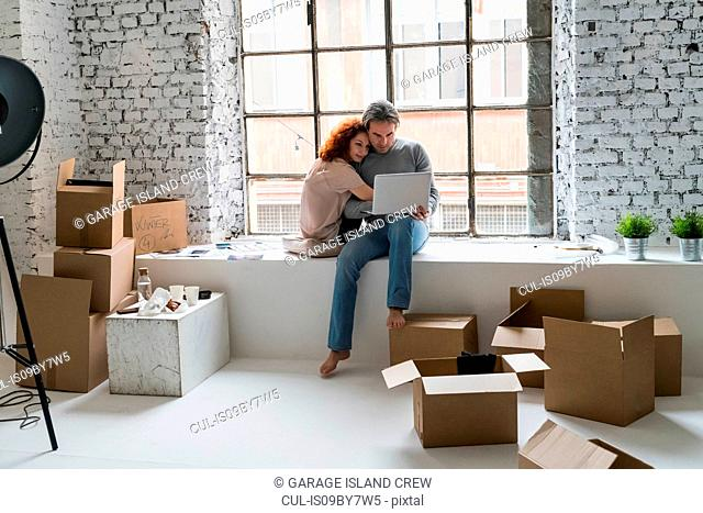 Romantic couple moving into industrial style apartment, sitting on window ledge looking at laptop