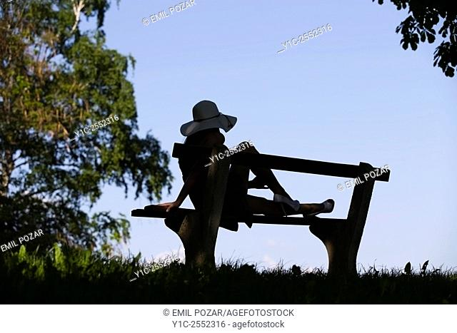 Young female on bench silhouetting against Blue sky