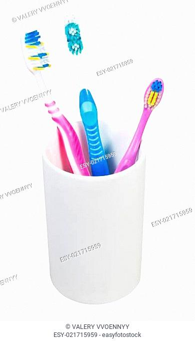 three toothbrushes in ceramic glass