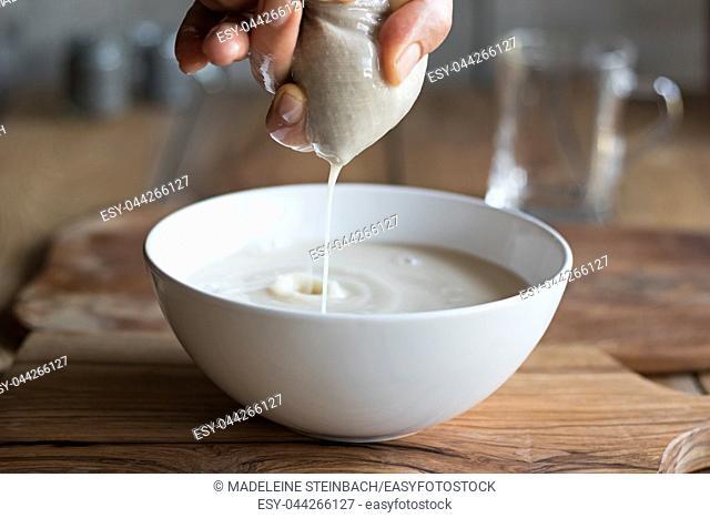 Preparation of nut milk - straining the milk through a milk bag into a bowl