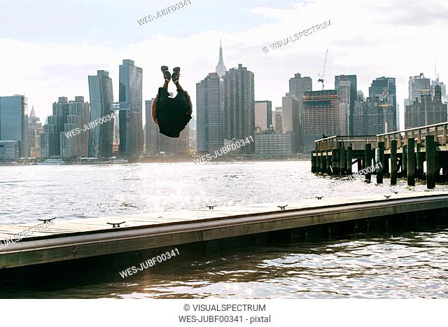 USA, New York, Brooklyn, young men doing backflip on pier in front of Manhattan skyline