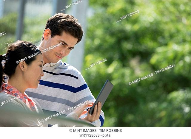 Summer in a city park. Business people on the move. A man and woman using a digital tablet, keeping in touch