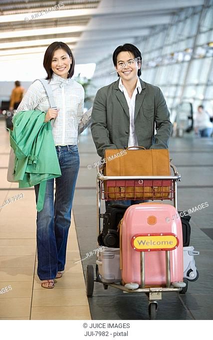 Couple pushing luggage trolley in airport, woman carrying green coat, smiling, front view, portrait