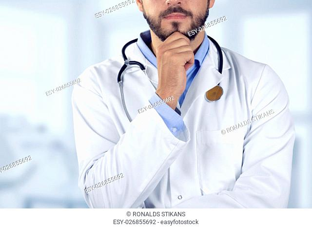 doctor standing with hand on chin