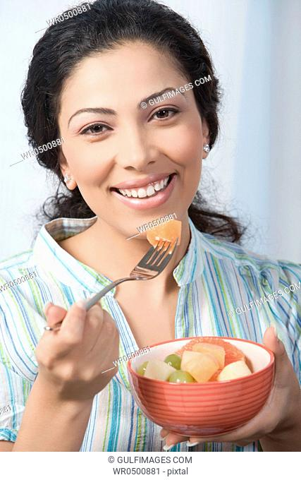 Young woman eating fruit salad, portrait