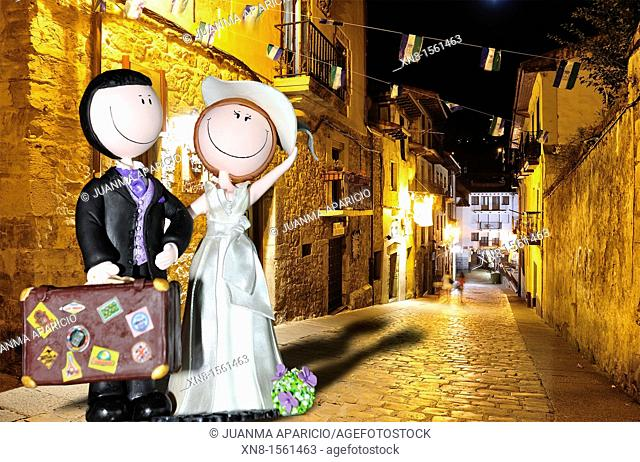 Dolls representing a newly married couple with a travel bag placed through photomontage on a street of the old Spanish city Laredo at night