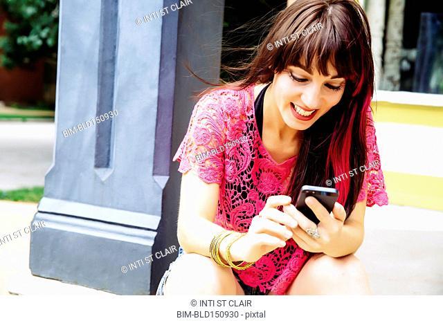 Caucasian woman using cell phone on sidewalk